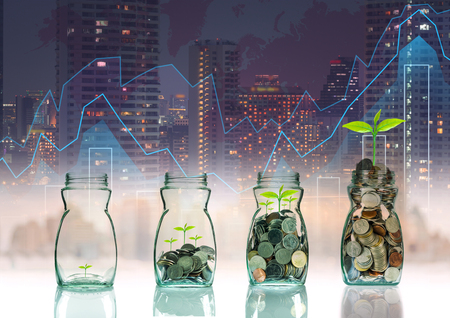 investment ideas: Mix coins and seed in clear bottle on trading graph with cityscape background,Business investment growth concept