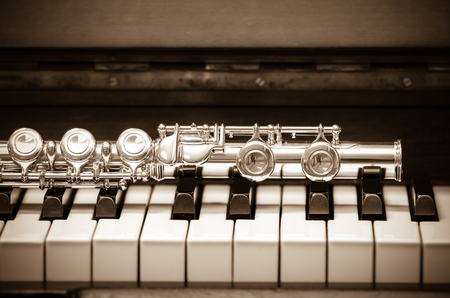professional flute: Closeup Flute on the keyboard of piano, musical instrument, vintage tone