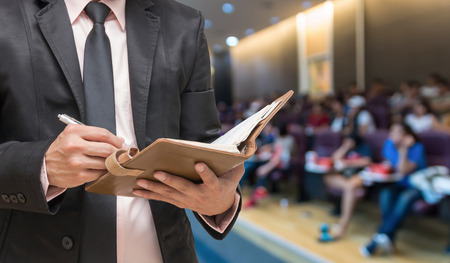 events: Businessman writing the note book on the Abstract blurred photo of conference hall or seminar room with attendee background Stock Photo
