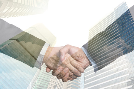 business handshake: double exposure handshake between businessman on Modern glass building background