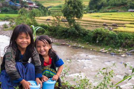 multiple ethnicity: MU CANG CHAI - SEP 25 : Undefined Vietnamese Hmong children smiling in rice terrace river side on september 25, 2015 at mu cang chai district,Yenbai province, northwest of Vietnam. Editorial