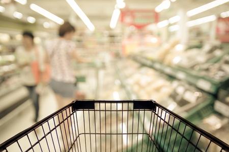 comida rica: Foto borrosa abstracta de la tienda con la carretilla en el departamento de fondo bokeh tienda