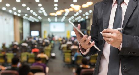 reuniones empresariales: Hombre de negocios usando la tableta en la foto borrosa abstracta de la sala de conferencias o sala de reuniones con el fondo de los asistentes Foto de archivo