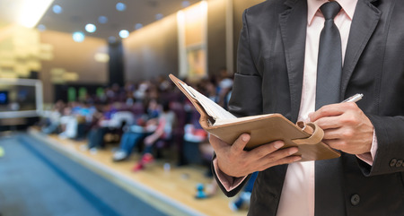 attendee: Businessman writing the note book on the Abstract blurred photo of conference hall or seminar room with attendee background Stock Photo