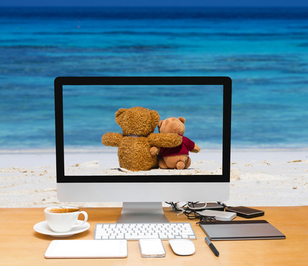Conceptual image of a workspace with computer desktop on two teddy bear brown color sitting on the beautiful beach with blue sea and sky