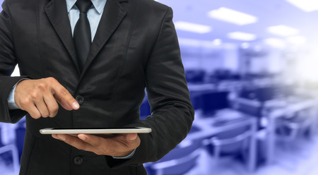 onderwijs: Zakenman met behulp van de tablet op Samenvatting vage foto van lege computer ruimte, onderwijs en business concept Stockfoto