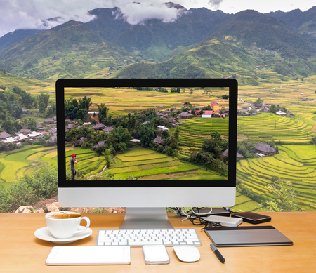 travel: Conceptual image of a workspace with computer desktop on Traveler take picture at Rice fields on terraced of Tu le District, YenBai province, Northwest Vietnam