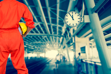 construction site: Asian engineers holding a yellow hardhat on abstract Blurred photo of sky train, transportation industrial concept Stock Photo