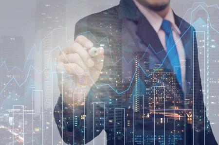 Doble exposición de hombre de negocios con el gráfico de Trading en el paisaje urbano de fondo, concepto financiero de negocios