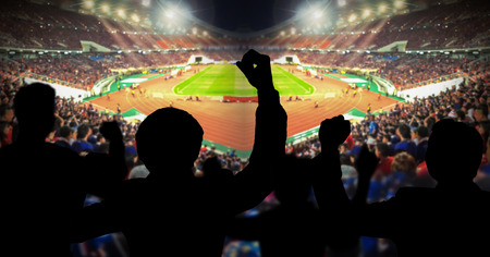 Silhouettes of football fans cheeringagainst large football stadium with lights, sport concept