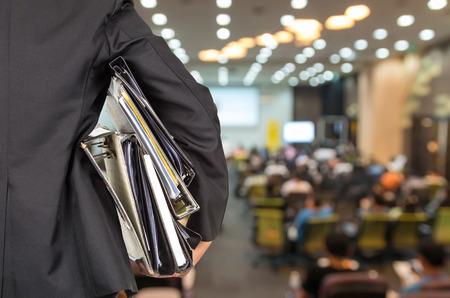 El hombre de negocios está llevando a cabo muchas carpetas de documentos sobre fondo de la foto borrosa de la sala de conferencias o sala de reuniones con el fondo de los asistentes, dorso, ocupado concepto de negocio Foto de archivo
