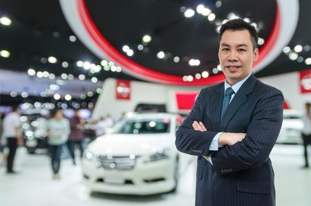 Vendeur de voitures heureux sur auto show fond flou, concept de transport Banque d'images