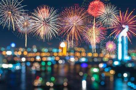 都市の景観にカラフルな花火は幻想的なお祭りの新年お祝いの夜に写真のボケ味がぼやけてください。