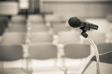 podium: Microphone on the speech podium over the Abstract blurred photo of conference hall or seminar room background