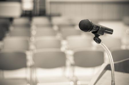 Mikrofon na podium mowy nad niewyraźne zdjęcie streszczenie sali konferencyjnej lub seminarium pokojowej tle Zdjęcie Seryjne