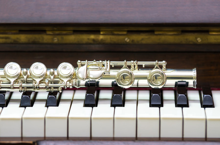 professional flute: Closeup Flute on the keyboard of piano, musical instrument Stock Photo
