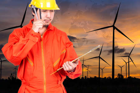 world thinking: Asian engineers thinking and holding the note pad on Wind turbine power generator with world map at twilight time, industrial concept, Elements of this image furnished by NASA