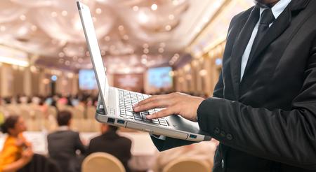 Zakenman met behulp van de laptop op de Kort wazig foto van de conferentiezaal of seminar kamer met genodigde achtergrond