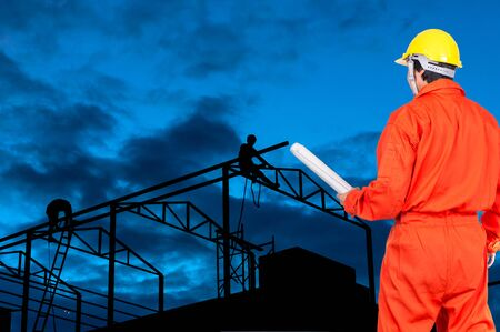 engineer: Asian engineers worker holding the blueprint on silhouette of Carpenter working on top of the roof structure, industrial concept