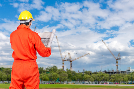 Portrait of Asian engineers looking at the blueprint on Under construction four cranes with cloud on blue sky, constructure industrial concept Stock Photo