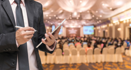 attendee: Businessman using the tablet on the Abstract blurred photo of conference hall or seminar room with attendee background Stock Photo