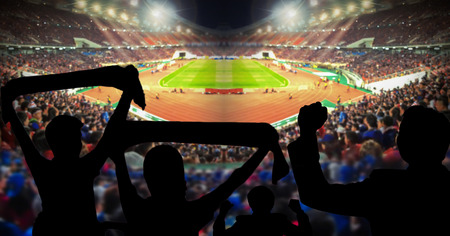 world sport event: Silhouettes of football fans cheering against large football stadium with lights, sport concept Stock Photo