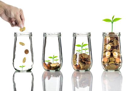 Main, mettre des pièces d'or dans une bouteille transparente sur fond blanc, concept de croissance de l'investissement des entreprises