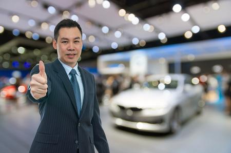 Vendeur de voitures heureux sur auto show fond flou, concept de transport