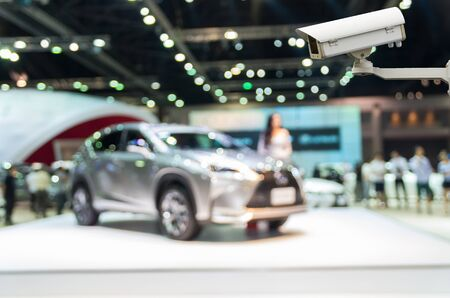 business security: CCTV security camera on monitor the Abstract blurred photo of motor show, car show room Stock Photo