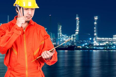 construction site: Asian engineers thinking and holding the note pad on Oil and gas refinery or Petrochemical factory at twilight time, industrial concept