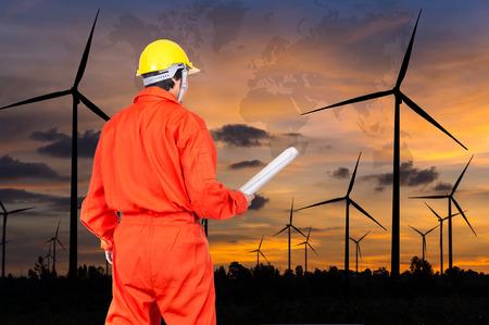 viento: Retrato de ingenieros asi�ticas que se sostienen en el modelo sobre generador de potencia de un aerogenerador con mapa del mundo en el tiempo crepuscular, concepto industrial, elementos de esta imagen proporcionada por la NASA