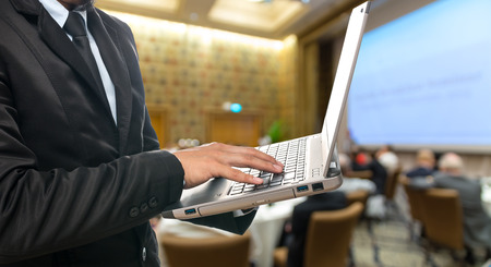 attendee: Businessman using the laptop on the Abstract blurred photo of conference hall or seminar room with attendee background