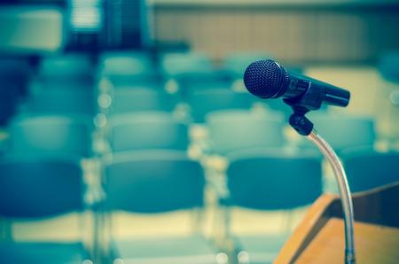 Microfono sul podio discorso sopra la foto astratta sfocata di sala conferenza o seminario stanza sfondo