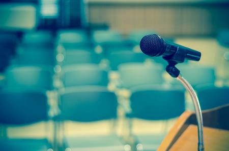 public speaker: Microphone on the speech podium over the Abstract blurred photo of conference hall or seminar room background