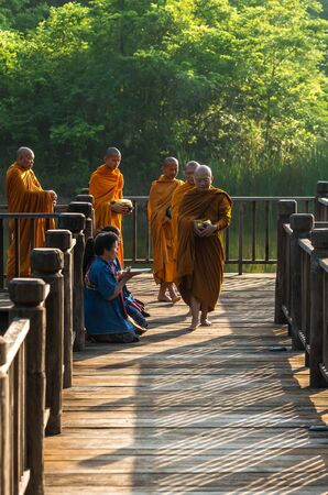 alms: NAKHON RATCHASIMA, THAILAND - OCTOBER 31: Undefined People are preparing food for alms to Buddhist monks on wooden walkway on October 31,2015 in Nakhon ratchasima, Thailand.