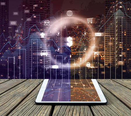 financial: Conceptual image of tablet on cityscape and financial graph with business logo background Stock Photo