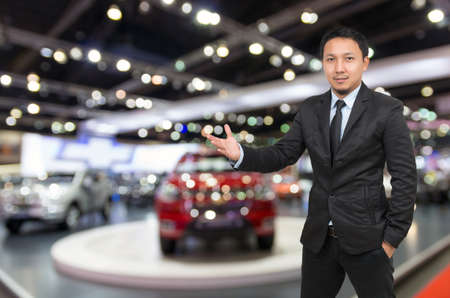 Happy car salesman on auto show blurred background, transportation concept