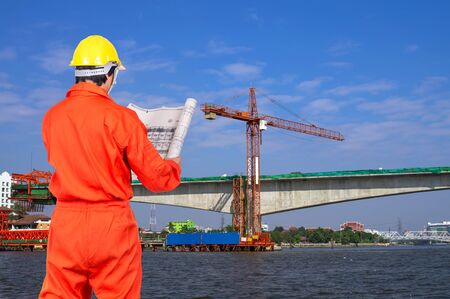 construction project: Portrait of Asian engineers looking at the blueprint on construction site worker over the river, industrial construction concept Stock Photo