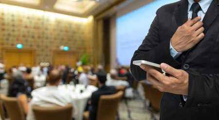 attendee: Businessman using the smart phone on the Abstract blurred photo of conference hall or seminar room with attendee background
