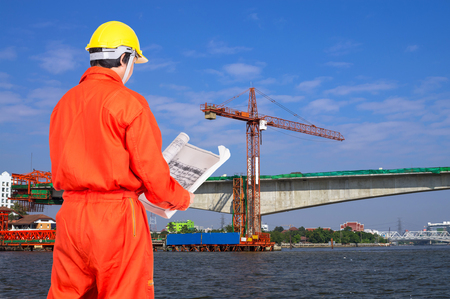 site: Portrait of Asian engineers looking at the blueprint on construction site worker over the river, industrial construction concept Stock Photo