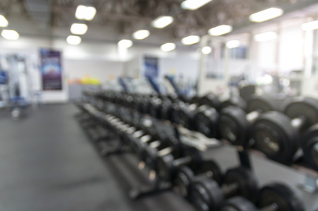 Abstract blurred photo of Dumbbells in modern luxury fitness center