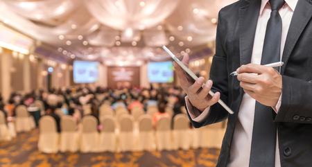 Geschäftsmann, die Tablette auf der Zusammenfassung unscharfen Foto Konferenzraum oder Seminarraum mit Teilnehmer Hintergrund mit
