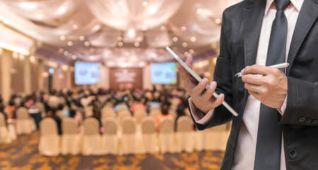 Businessman using the tablet on the Abstract blurred photo of conference hall or seminar room with attendee background Standard-Bild