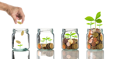 clear bottle: Hand putting gold coins into clear bottle on white background,Business investment growth concept