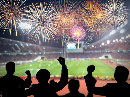 cheering fans: Silhouettes of football fans cheering against large football stadium with colorful fireworks, sport concept
