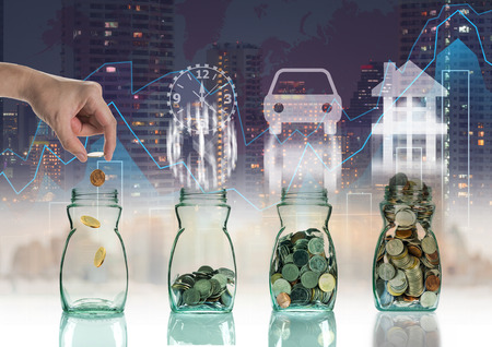 investment concept: Hand putting mix coins in clear bottle on trading graph with cityscape background with sign shape,Business investment growth concept