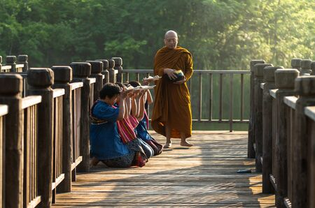 undefined: NAKHON RATCHASIMA, THAILAND - OCTOBER 31: Undefined People are preparing food for alms to Buddhist monk on wooden walkway on October 31,2015 in Nakhon ratchasima, Thailand. Editorial