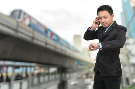businessman waiting call: Young businessman talking on mobile phone and looking at watch on abstract Blurred photo of sky train with traffic and cityscape, business rush hour concept