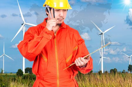 world thinking: Asian engineers thinking and holding the note pad on Wind turbine power generator with world map, industrial concept, Elements of this image furnished by NASA Stock Photo