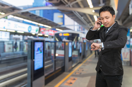 businessman waiting call: Young businessman talking on mobile phone and looking at watch on Abstract blurred photo of sky train station with people background, business rush hour concept